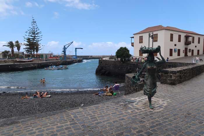 Muelle del Puerto de la Cruz con estatua de pescadora, la Casa de la Aduana y la playa